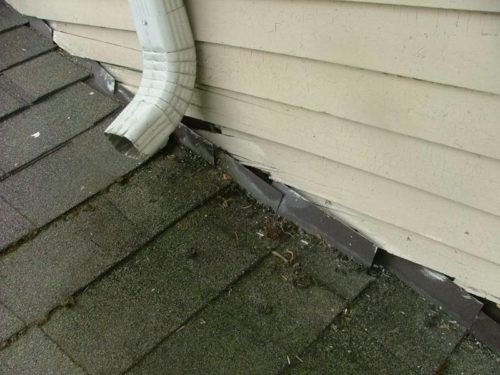 Downspout Draining To Roof With Siding Damage Obvious