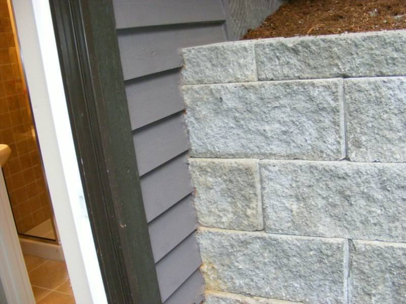 Retaining wall installed over the top of the siding