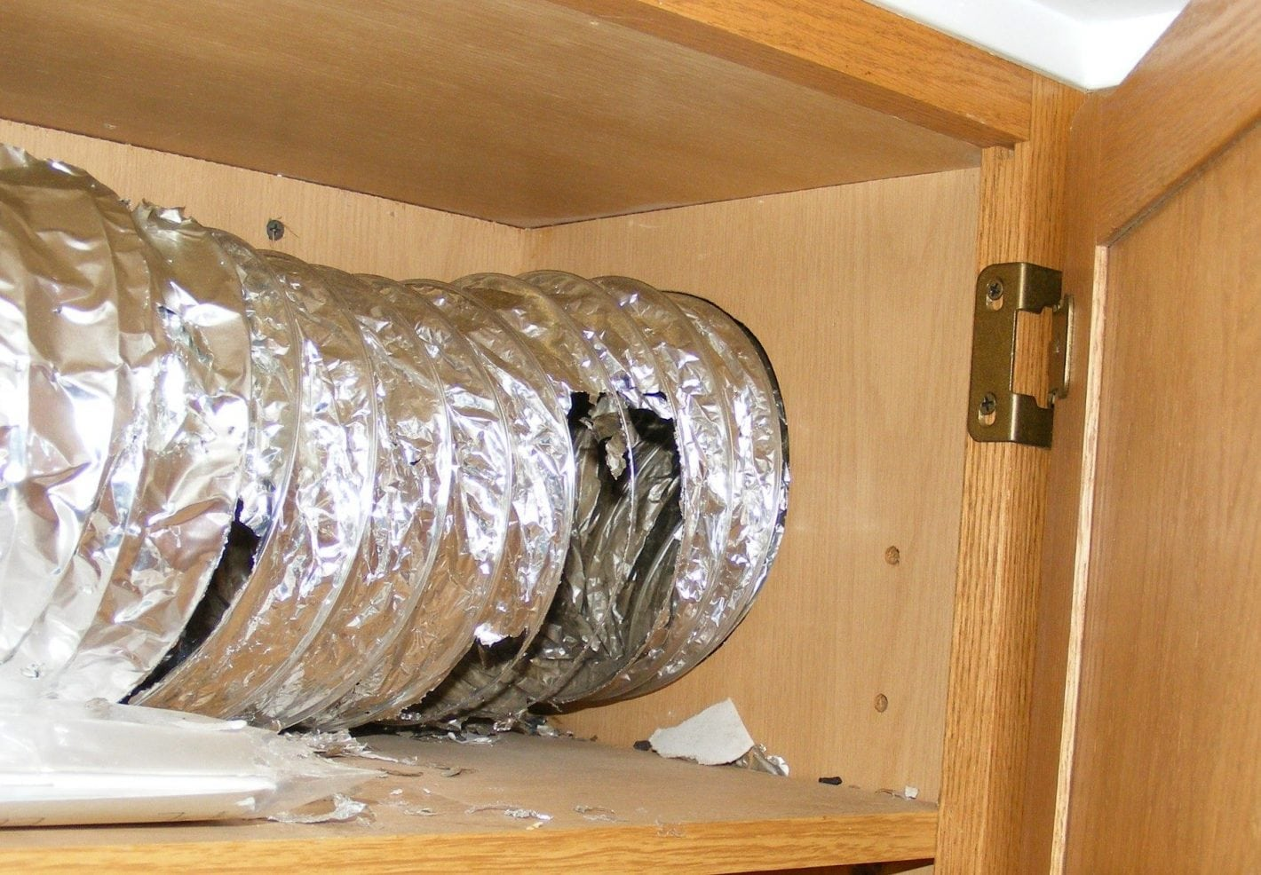 Rodent damaged ductwork in a kitchen cabinet