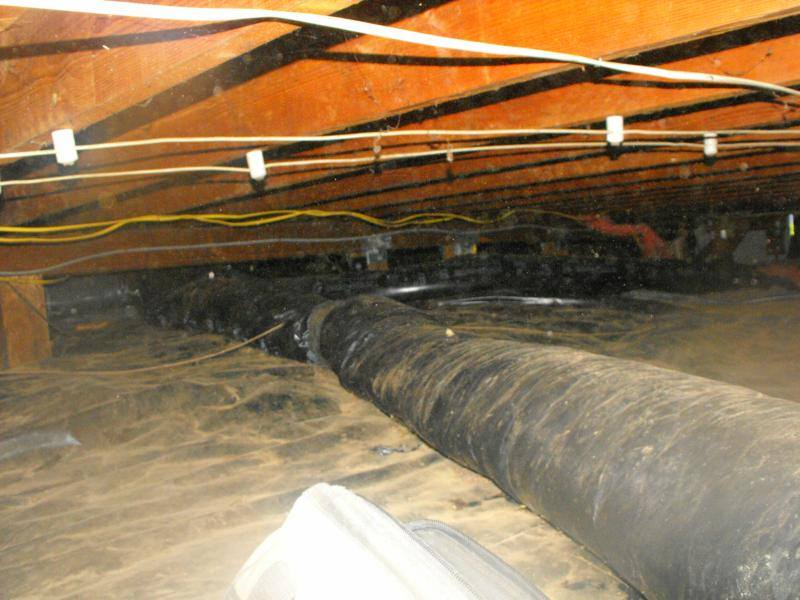 Flexible ductwork on the ground in a crawl space