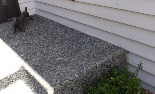 Siding behind the concrete stoop